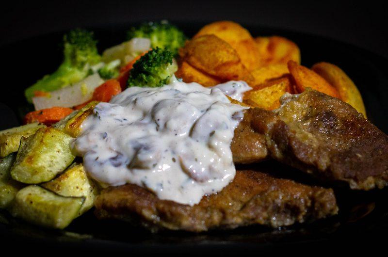 Sült sertéstarja, sült cukkinivel, sült, fűszeres burgonyával, párolt zöldségekkel és gombaszósszal